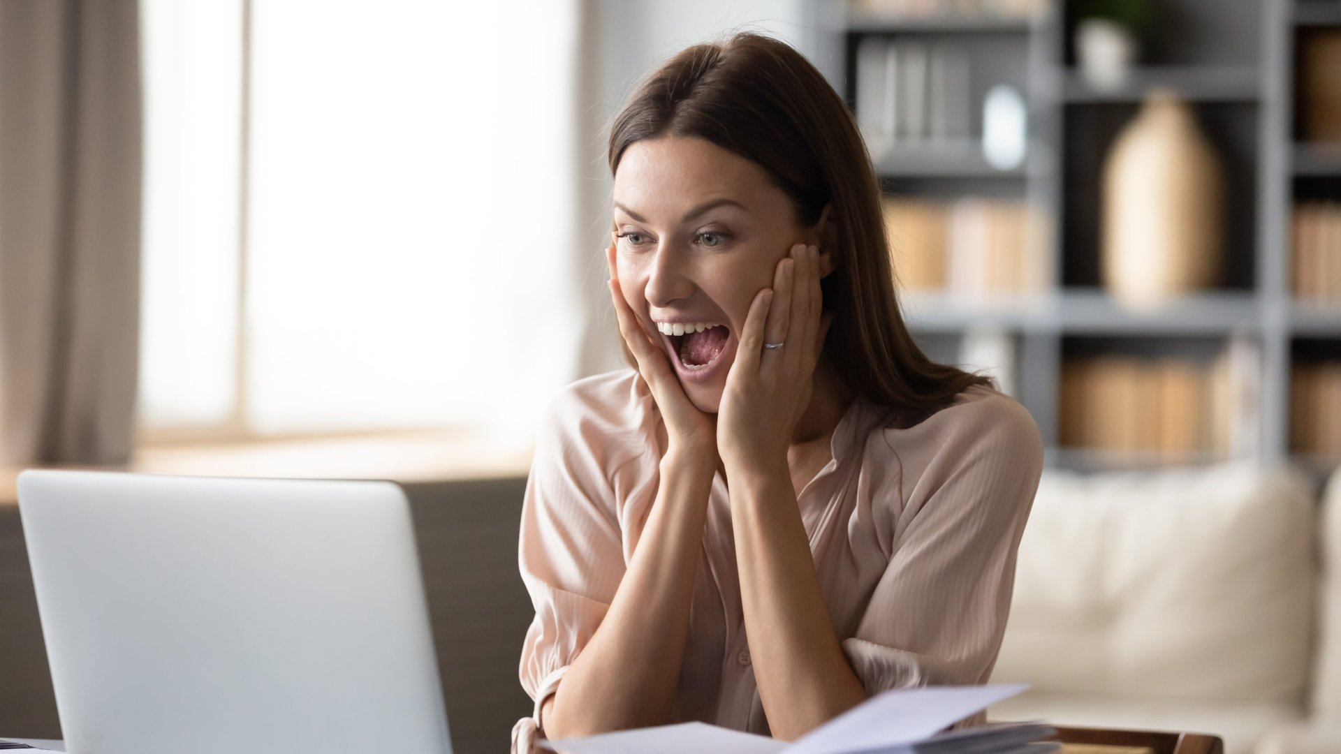excited woman looking at laptop