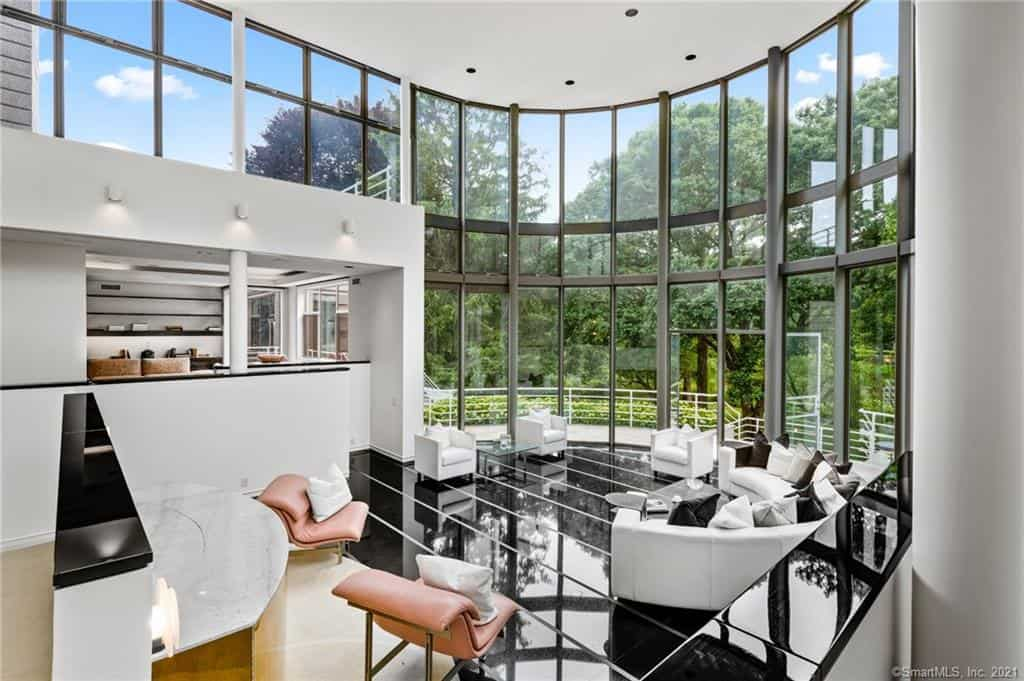 The dramatic living room has a two-story tall glass wall that serves as a backdrop to the living area.