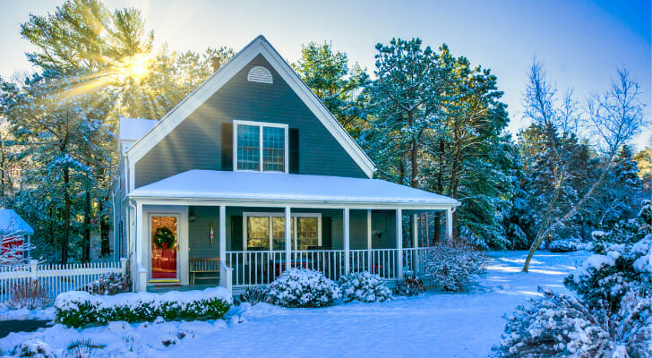 Image shows a suburban home with a snow-covered lawn and trees surrounding it. In this study, SmartAsset found the salary needed to afford home payments in the 15 largest U.S. cities.
